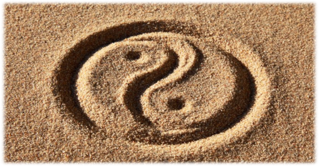 Photo of Yin and Yang Symbol Drawn in the Sand